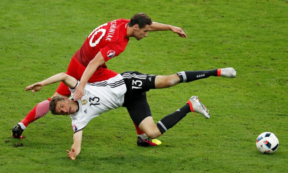 Germany's Thomas Muller in action with Poland's Grzegorz Krychowiak. REUTERS/Charles Platiau Livepic