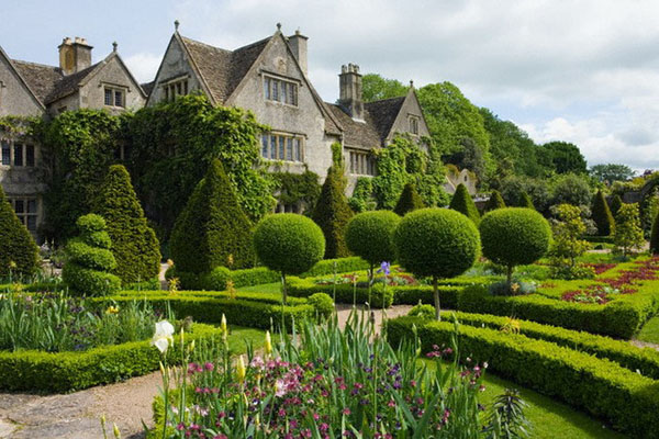 Malmesbury, England, UK --- Early summer at the Abbey House Garden, with the Manor House across the knot garden. --- Image by © Mark Bolton/Corbis